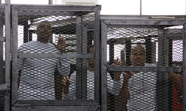 Jailed al-Jazeera journalists Mohamed Fahmy, Baher Mohamed and Peter Greste in a cage