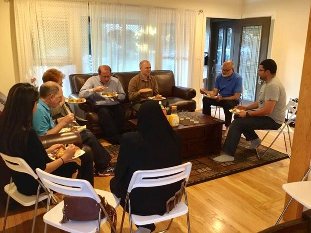 Yusra and her guests enjoying homemade food and open conversation. Photo Credit: Dine With a Muslim Family/ Facebook